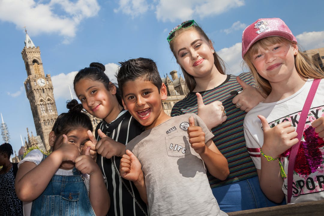 Children in Bradford City Park giving the thumbs up