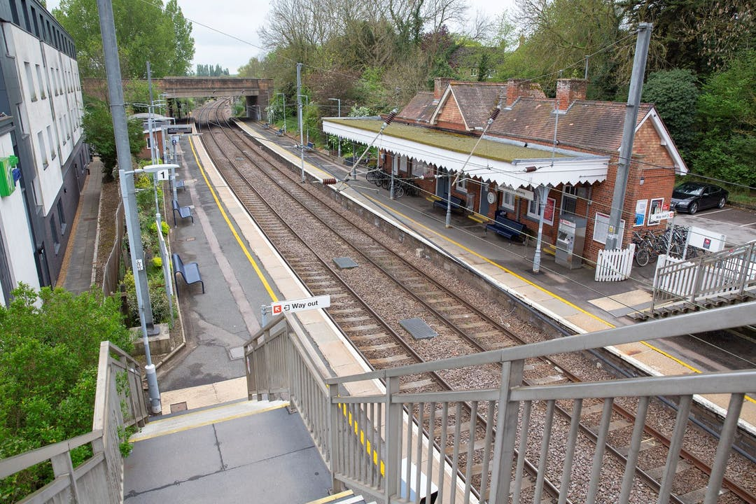 Whittlesford Parkway station view of tracks and station building from footbridge with Holiday Inn on left-hand side