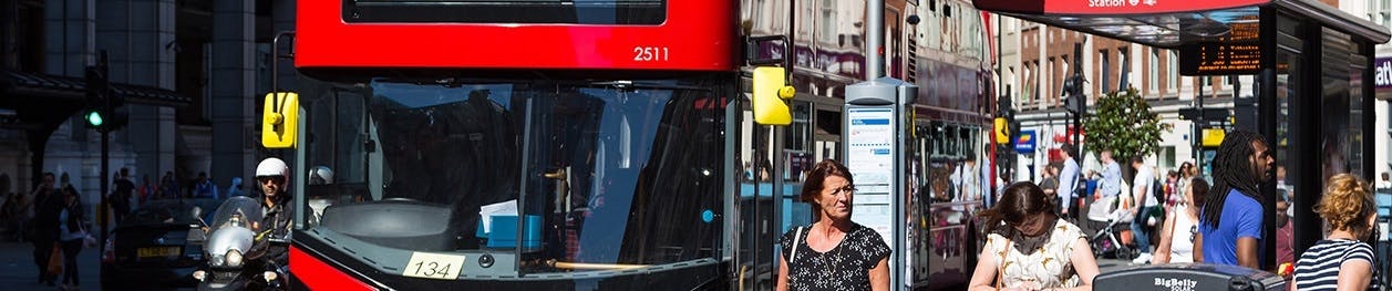 Passengers waiting at bus stop on high street