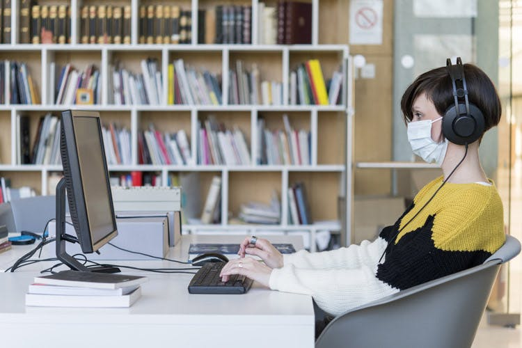 Photo of a person sitting at a computer in a library