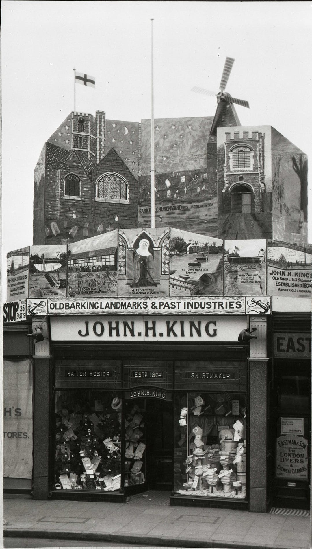 The shop front of John H King's Draper's - with a huge art display above the shop - showing landmark buildings and trades from Barking's heritage - to celebrate the Barking Town Charter of 1931.