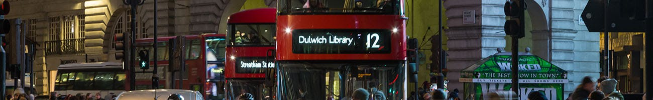 Three red London Buses driving through central London at night