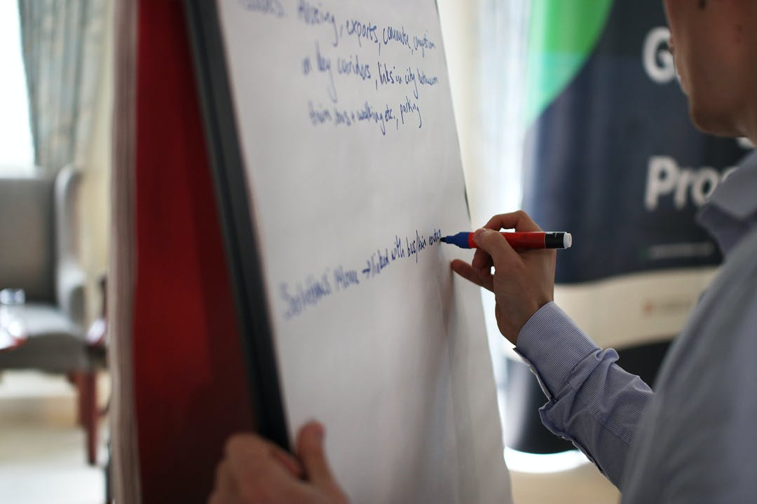 Person writing on a flip chart at an event