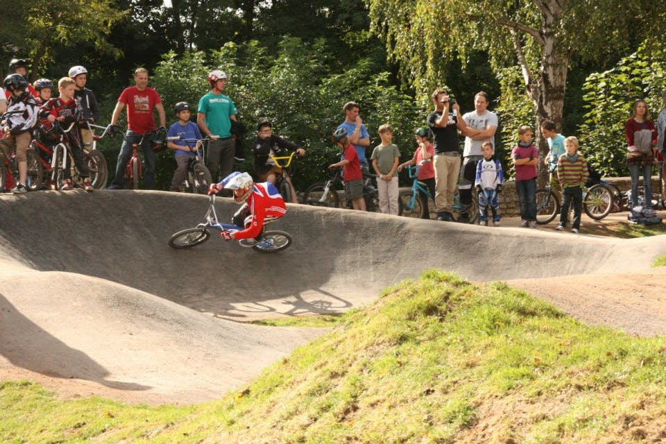 BMX biker using a pump track, watched by bystanders.