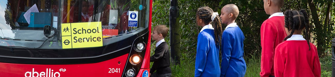 Young people boarding a London bus to travel to school