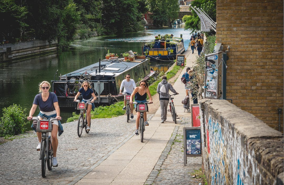 An image of people cycling along a canal.