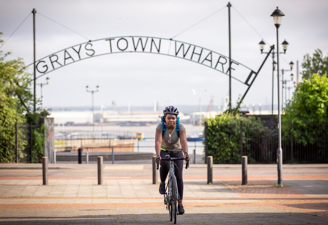A woman smiles whilst riding a bike, she is wearing a grey tshirt and black leggings with a cycle helmet.  Behind her you can see the entrance to Grays Town Wharf and the river Thames beyond.