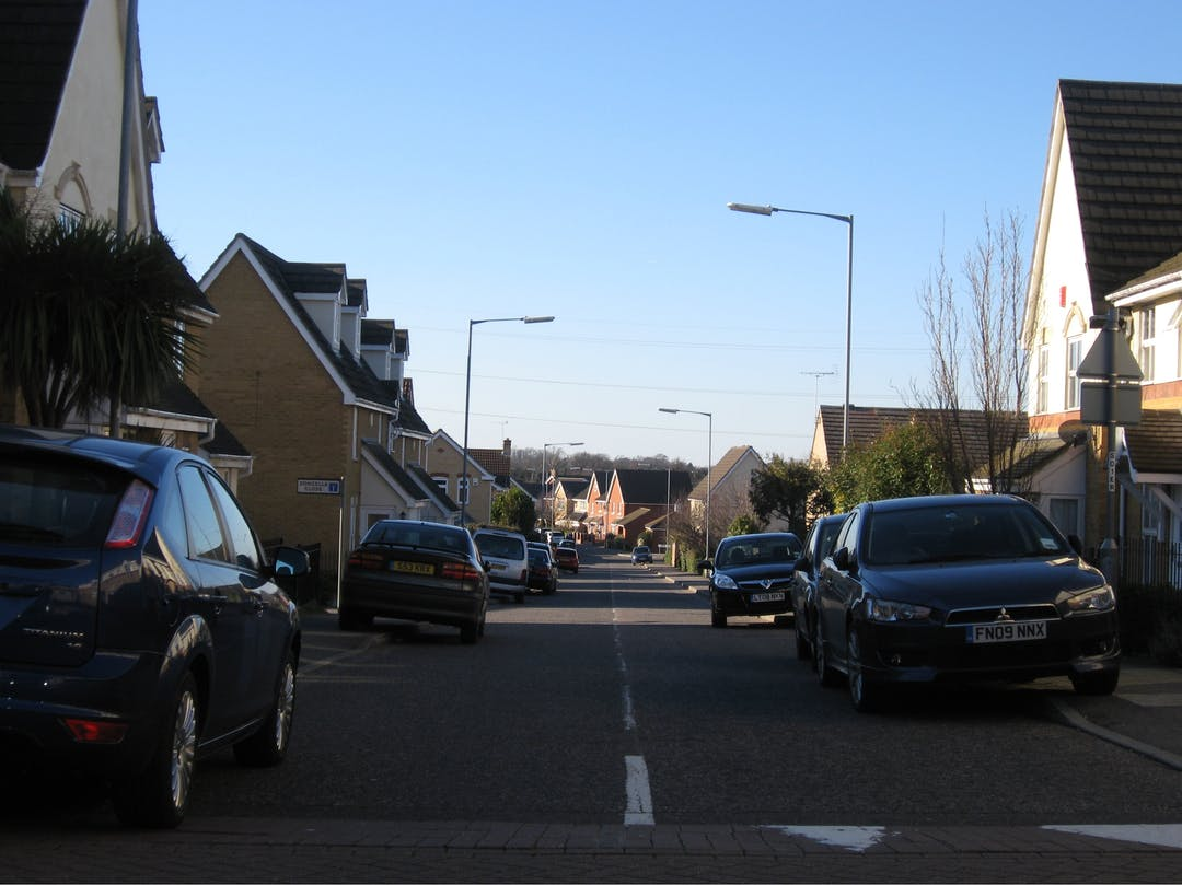 A photograph taken in the middle of the road, looking down the street you can see cars parked up on the pavement causing an obstruction on both sides of the road.  A speed bump is in the road.