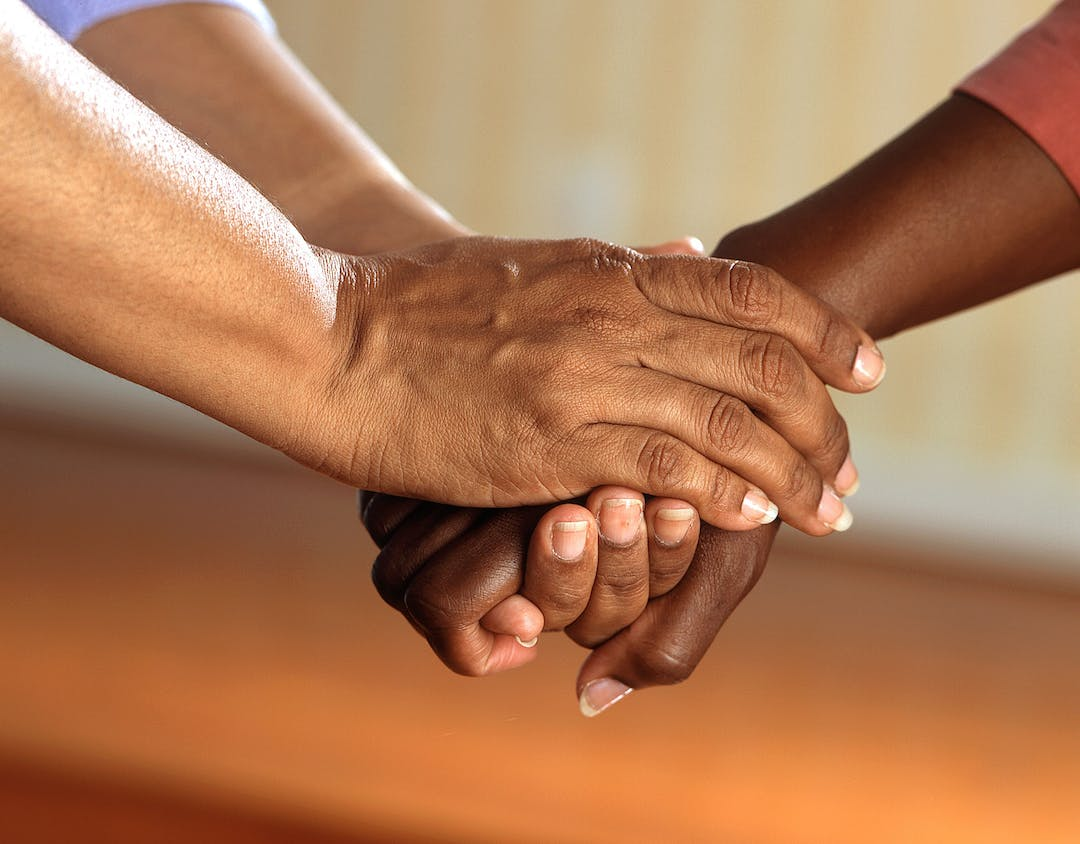 A photo of two people holding hands