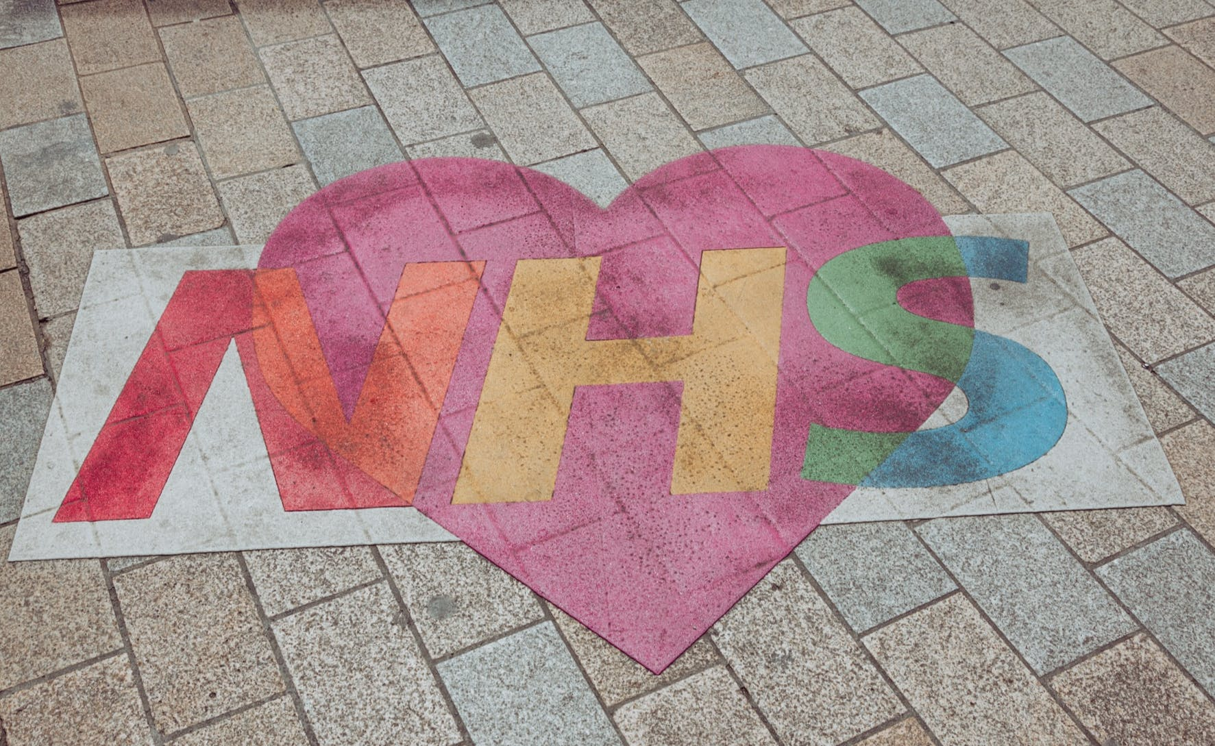 multicolour NHS logo on paved floor with a heart overlaid on top