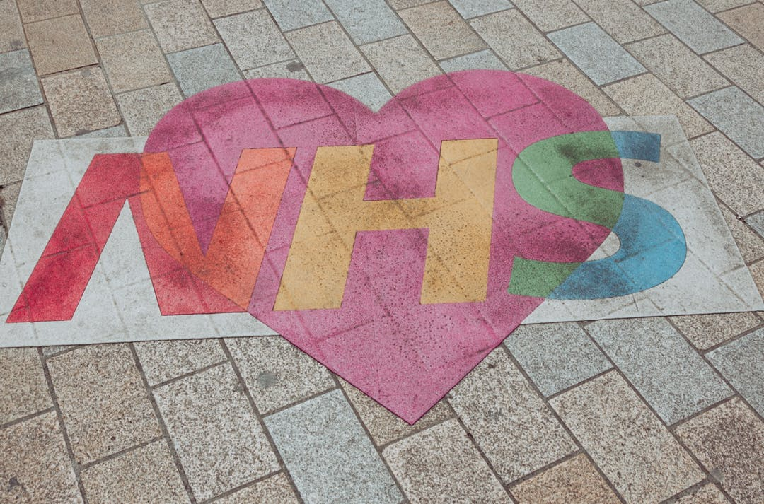 Image of the NHS logo painted in multicolour with a heart overlaid on a tiled floor.