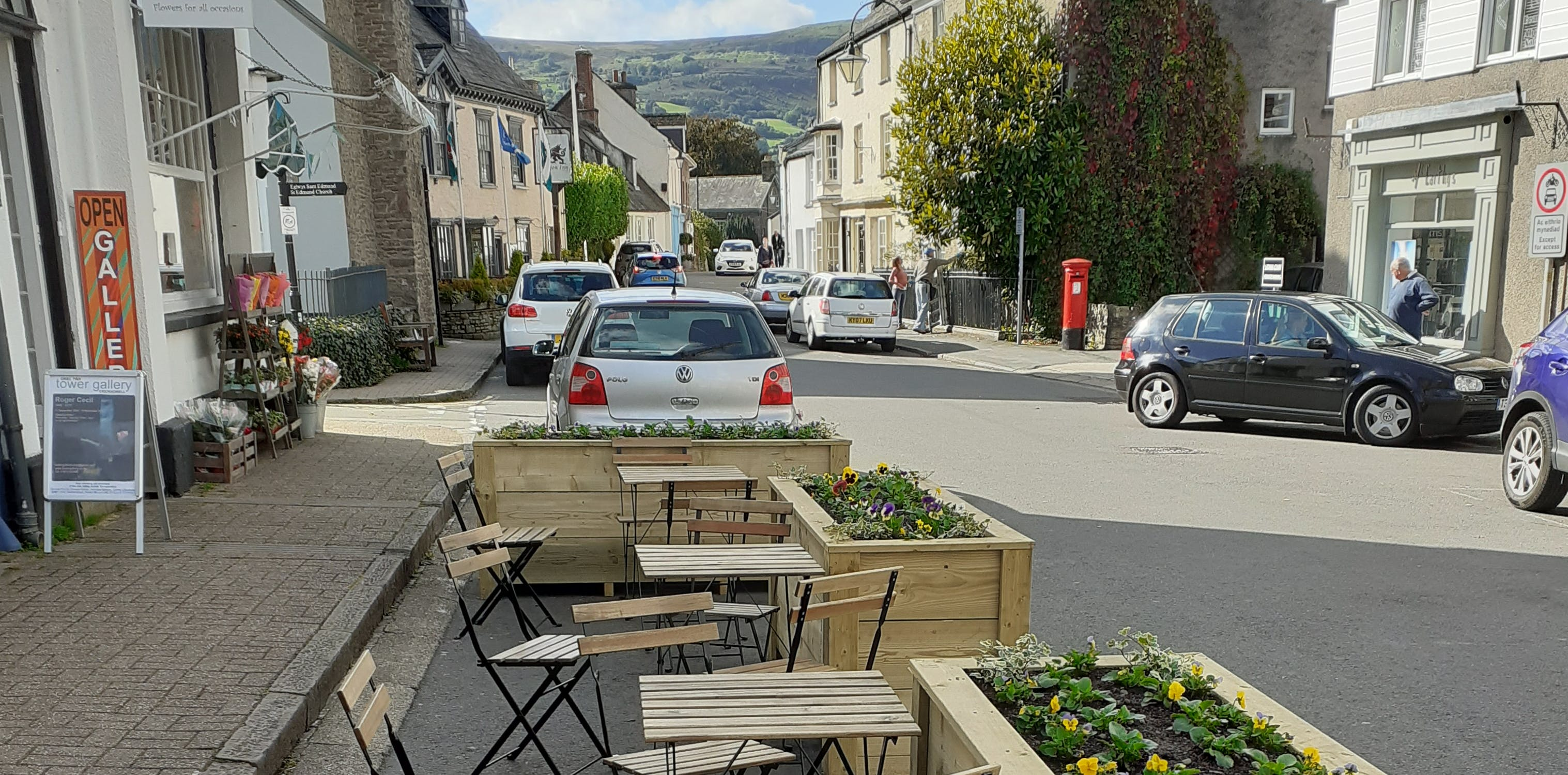 Image of table and chairs outside on the street surrounded by planters.