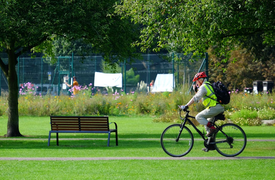 A man in hi-vis vest and cycling helmet, cycling through Jesus Green