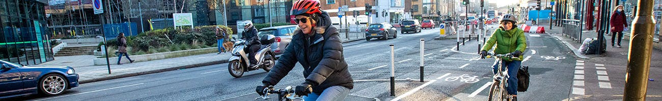 Two people cycling on Greenwich to Woolwich cycle lane