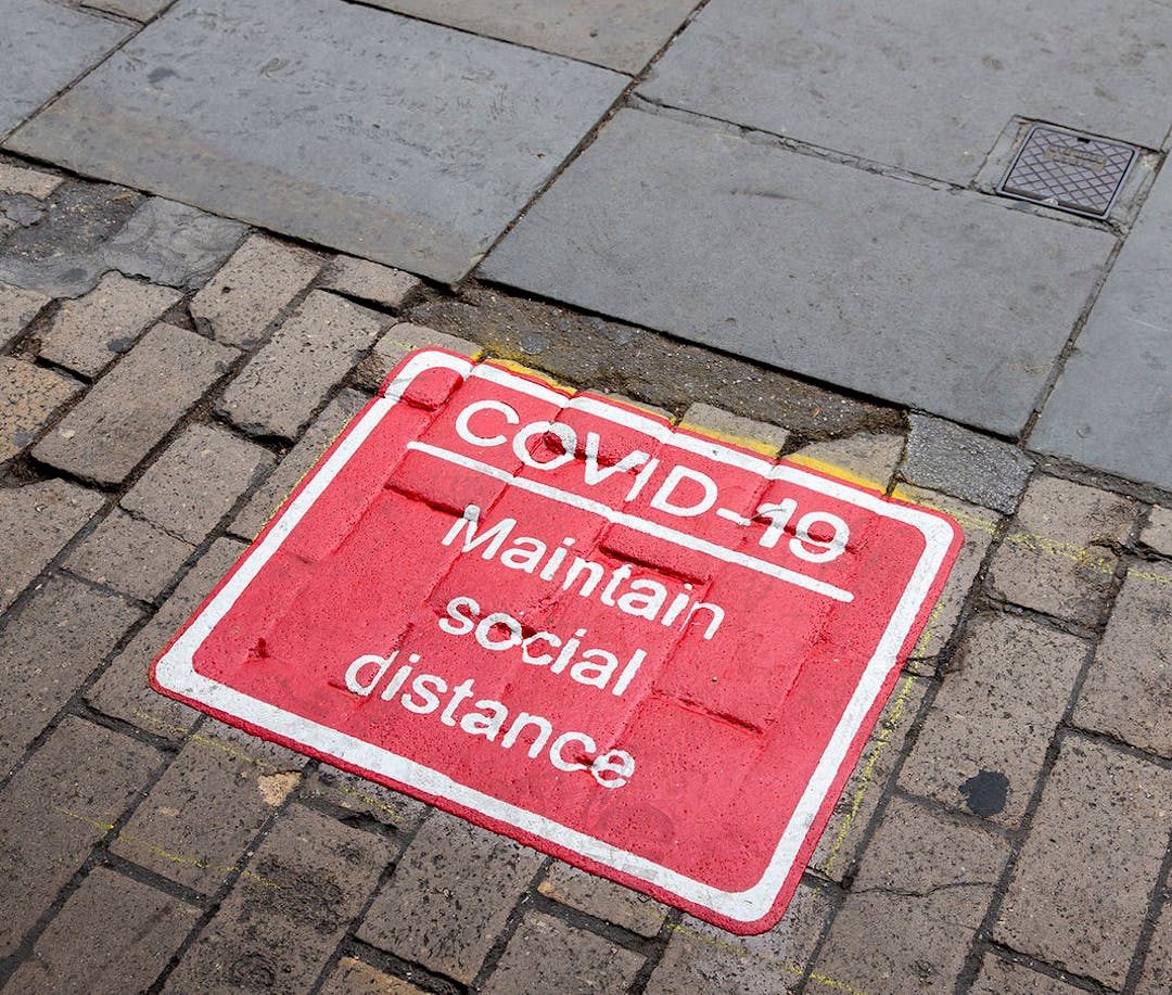 "A Covid-19 pavement marking.  White text on a red square, saying ""Covid-19 - Maintain Social Distance"""