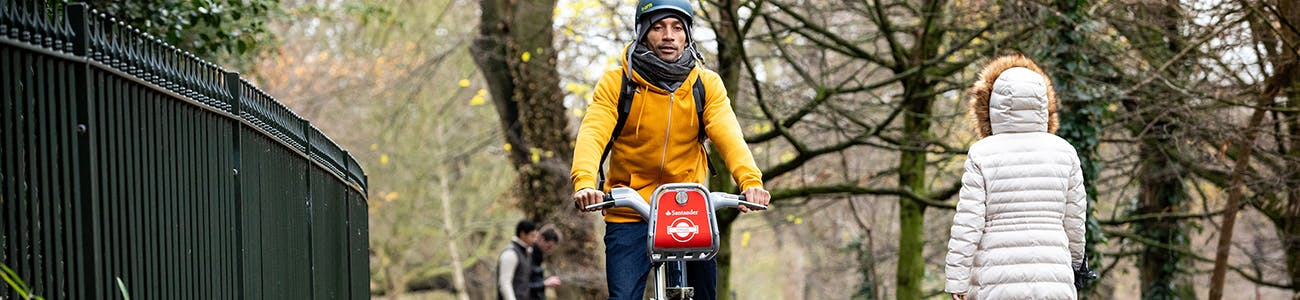 Image of man cycling in a park on a Santander Cycle Hire bike