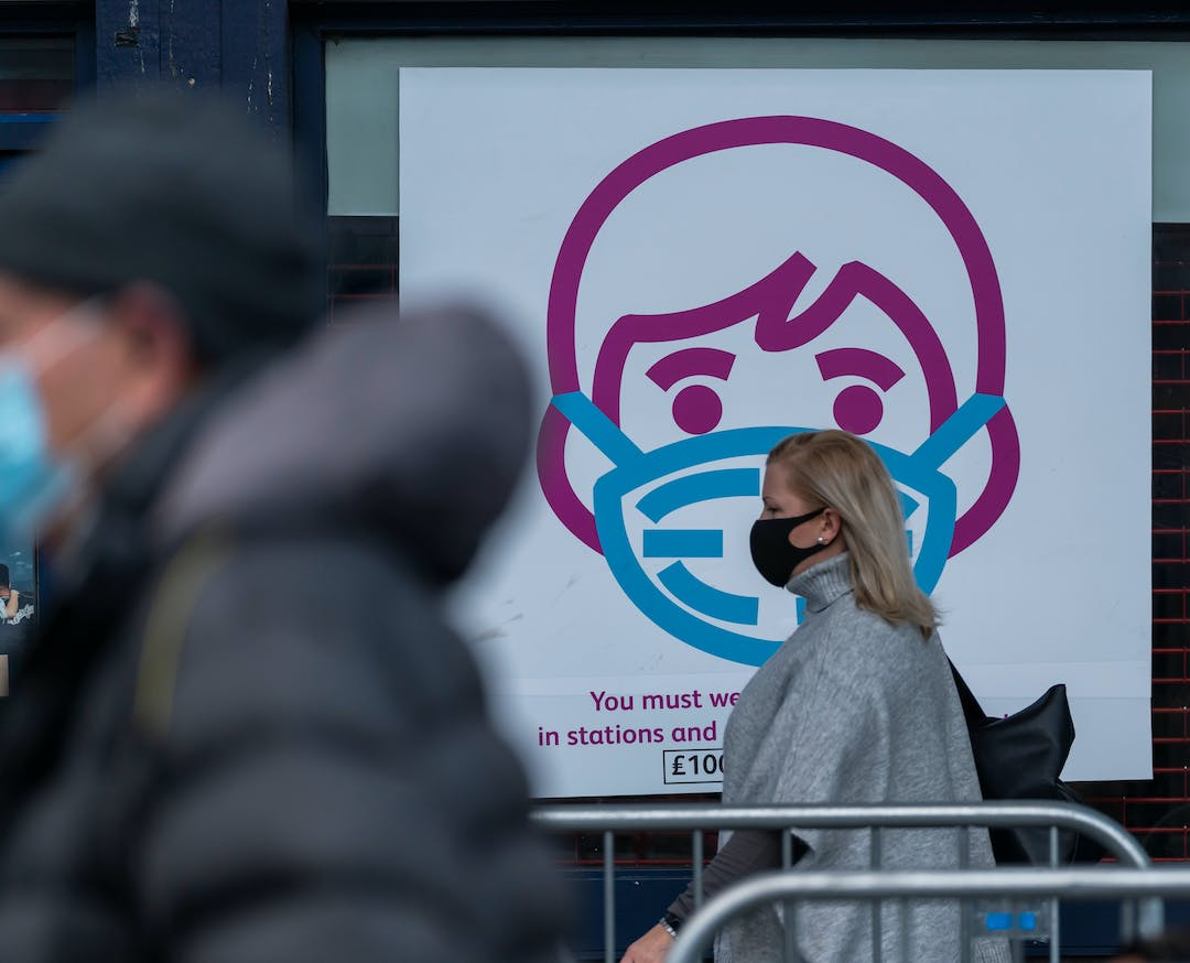 Scene in front of Barking Station showing a sign encouraging people to wear face masks