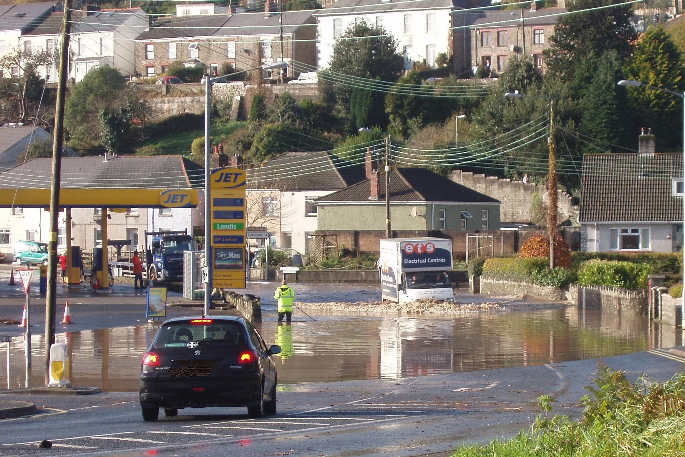 Deep flood water covering the A390 in front of the Jet garage.