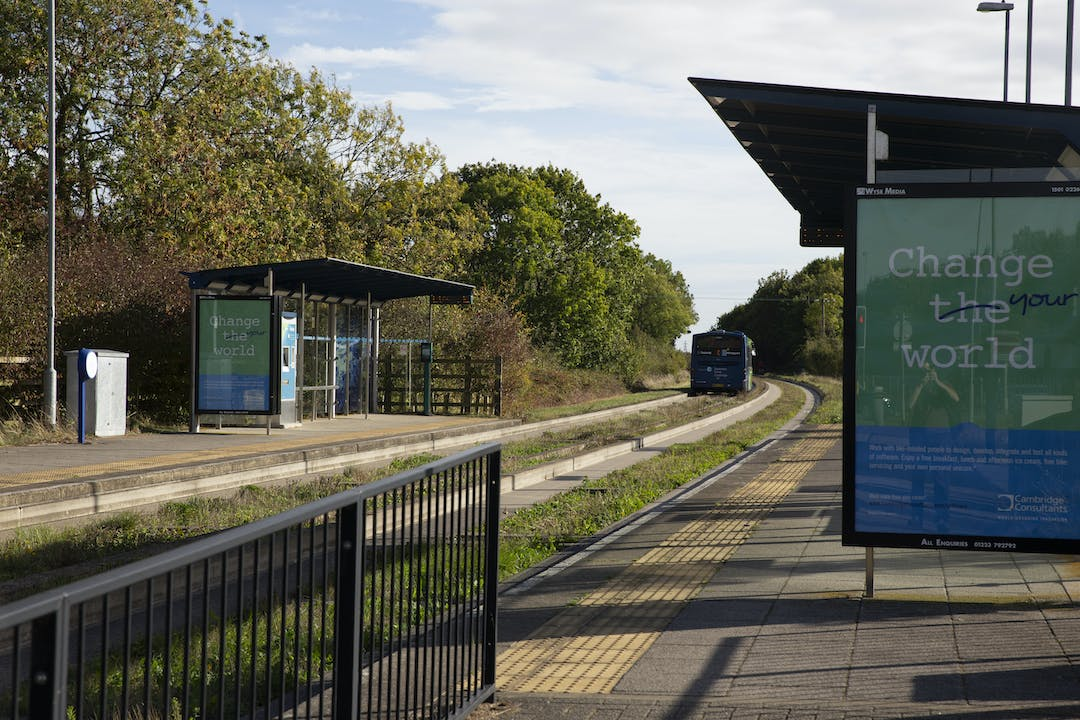 Oakington Busway stop. Bus shelters on either side of the Busway track, with a bus driving away from the shelter on the left-hand side