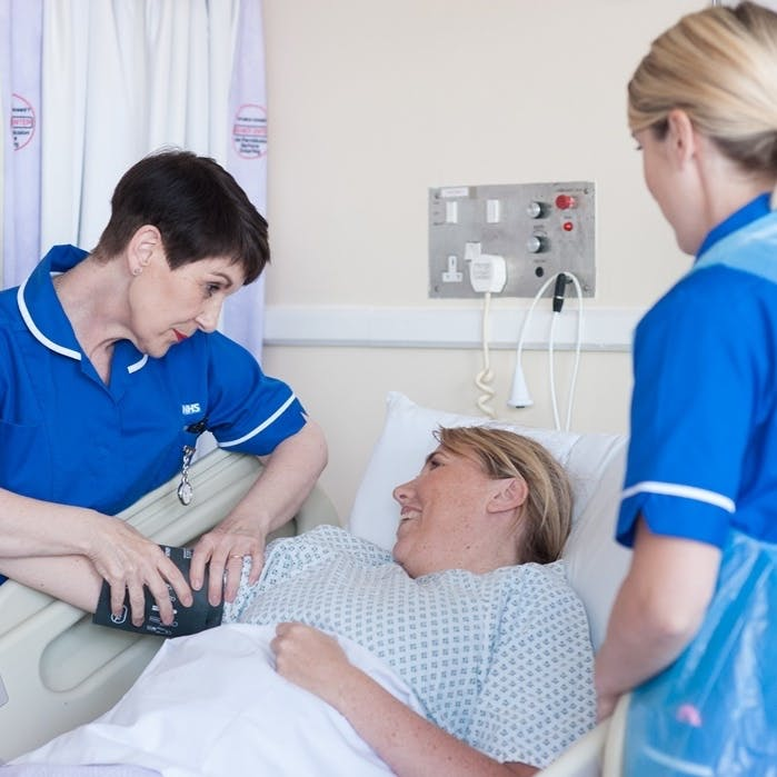 Hospital services - two nurses pictured treating a patient